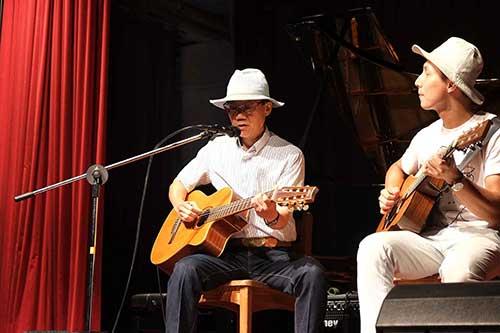 穿著白襯衫的吉他手彈著吉他