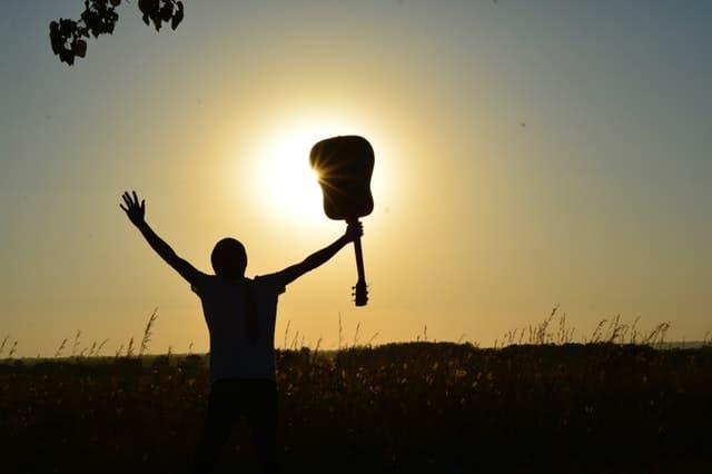 在夕陽下拿著吉他歡呼的男人